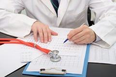 Medico che controlla una carta di Ecg Immagine Stock