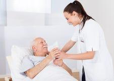 Medico che dà bicchiere d'acqua all'uomo senior Fotografie Stock Libere da Diritti