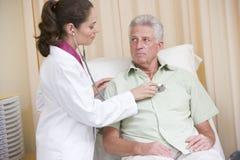 Medico che dà controllo con lo stetoscopio all'uomo Fotografia Stock Libera da Diritti