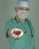 Medico che dà le capsule di colore rosso Fotografie Stock Libere da Diritti