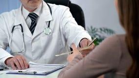 Medico che dà prescrizione del farmaco al paziente, alla diagnosi qualificata ed al trattamento immagine stock libera da diritti