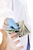 Medico che dà soldi Immagini Stock