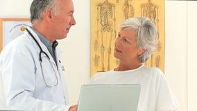 Medico che dà una spiegazione al suo paziente archivi video