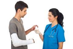 Medico che dà le medicine all'uomo danneggiato Fotografie Stock