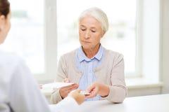 Medico che dà prescrizione e farmaco alla donna Fotografie Stock