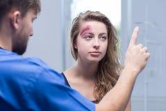 Medico che diagnostica donna danneggiata Fotografia Stock