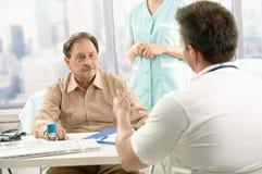 Medico che discute diagnosi con il paziente Fotografie Stock