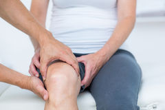 Medico che esamina il suo ginocchio dei pazienti Immagini Stock