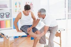 Medico che esamina il suo ginocchio paziente Fotografie Stock