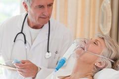 Medico che esamina il suo paziente Fotografie Stock Libere da Diritti