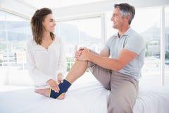 Medico che esamina il suo piede paziente immagine stock