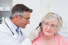 Medico che esamina l'orecchio femminile dei pazienti con l'otoscopio fotografia stock