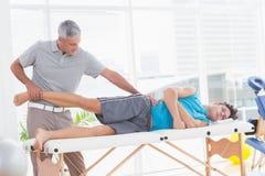 Medico che esamina la sua gamba paziente Fotografie Stock