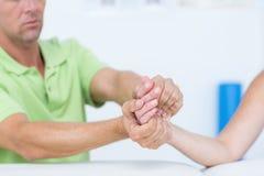 Medico che esamina la sua mano dei pazienti Fotografie Stock Libere da Diritti