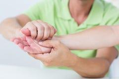 Medico che esamina la sua mano dei pazienti Fotografie Stock