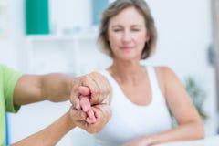 Medico che esamina la sua mano dei pazienti Immagine Stock Libera da Diritti