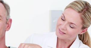 Medico che esamina la sua parte posteriore del paziente stock footage