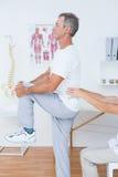 Medico che esamina la sua parte posteriore del paziente Immagine Stock
