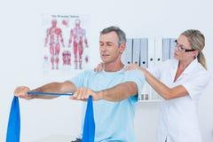 Medico che esamina la sua parte posteriore del paziente Fotografie Stock