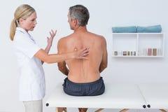 Medico che esamina la sua parte posteriore del paziente Immagini Stock Libere da Diritti