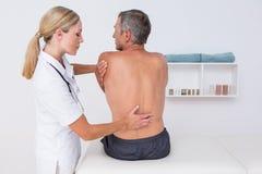 Medico che esamina la sua parte posteriore del paziente Fotografia Stock Libera da Diritti