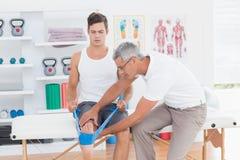 Medico che esamina le sue gambe della parte posteriore del paziente Fotografia Stock Libera da Diritti