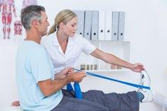 Medico che esamina le sue gambe della parte posteriore del paziente Fotografia Stock