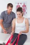 Medico che esamina le sue gambe della parte posteriore del paziente Fotografie Stock