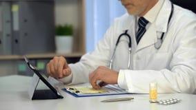 Medico che esamina modulo di iscrizione, trattamento di prescrizione online, consulente fotografie stock libere da diritti