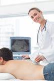 Medico che esegue la ricerca di ultrasuono sopra appoggia del paziente Immagini Stock
