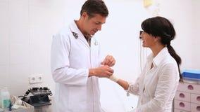 Medico che fa una fasciatura al polso paziente stock footage