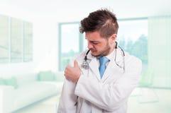 Medico che ha problemi di dolore della spalla sul lavoro Immagini Stock Libere da Diritti