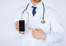 Medico che indica allo smartphone Immagini Stock