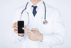 Medico che indica allo smartphone Fotografia Stock Libera da Diritti