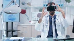 Medico che indossa un funzionamento della cuffia avricolare di VR nello spazio virtuale nel suo ufficio del moder stock footage