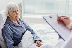 Medico che interroga donna anziana in ospedale fotografia stock libera da diritti