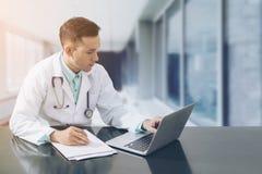 Medico che lavora allo scrittorio con il computer portatile Fotografie Stock Libere da Diritti