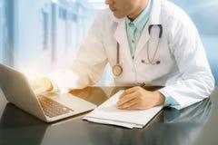 Medico che lavora allo scrittorio con il computer portatile Immagine Stock Libera da Diritti