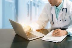 Medico che lavora allo scrittorio con il computer portatile Fotografia Stock Libera da Diritti