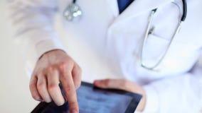 Medico che lavora con la ricerca dei raggi x sul pc della compressa video d archivio