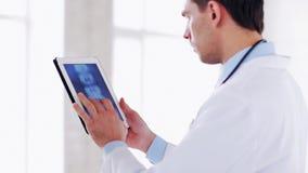 Medico che lavora con la ricerca dei raggi x sul pc della compressa archivi video