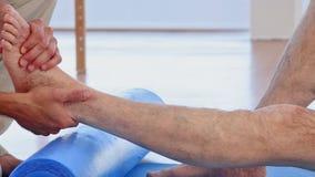 Medico che massaggia la sua caviglia dei pazienti video d archivio
