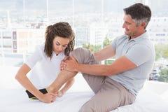 Medico che mette il gancio di caviglia al suo paziente fotografie stock