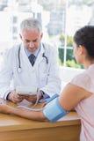 Medico che misura il battito cardiaco di un paziente fotografia stock