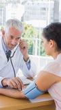 Medico che misura la pressione sanguigna del suo paziente immagine stock