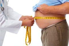 Medico che misura lo stomaco obeso dell'uomo Fotografie Stock Libere da Diritti