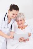 Medico che mostra compressa digitale al paziente immagini stock libere da diritti