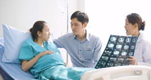 Medico che mostra i valori dei raggi x alla donna incinta ed al suo marito con emozione seria stock footage