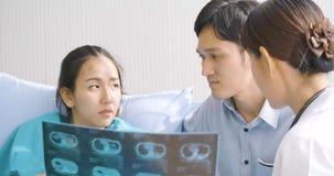 Medico che mostra i valori dei raggi x alla donna incinta ed al suo marito con emozione seria archivi video