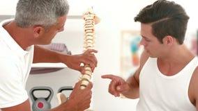 Medico che mostra il modello della spina dorsale al paziente archivi video